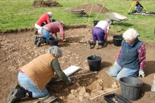 Digging the Parterre at Campden House, Autumn 2016. Picture shows five volunteers trowelling in a shallow trench.