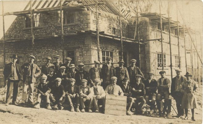 Group of workmen outside house construction. Board reads 'Glostershire County Council Small Holdings, Campden'