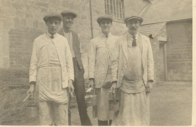 Four Painters and decorators in yard outside building