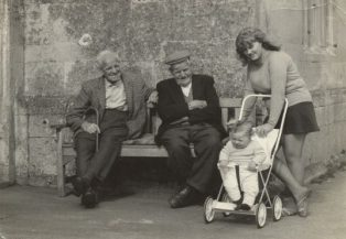 Two men on bench outside almshouse