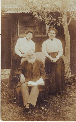 Man seated, two women standing behind