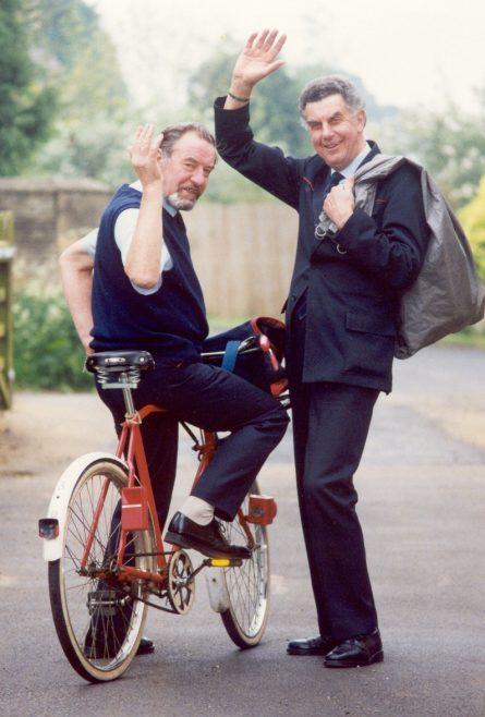Two postmen waving goodbye
