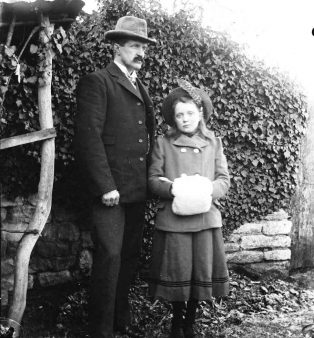 Jesse and his daughter, Dorothy, outdoors. She is holding a white fur muff and wearing a knitted tam o'shanter. He wears a dark suit and a Homburg hat.